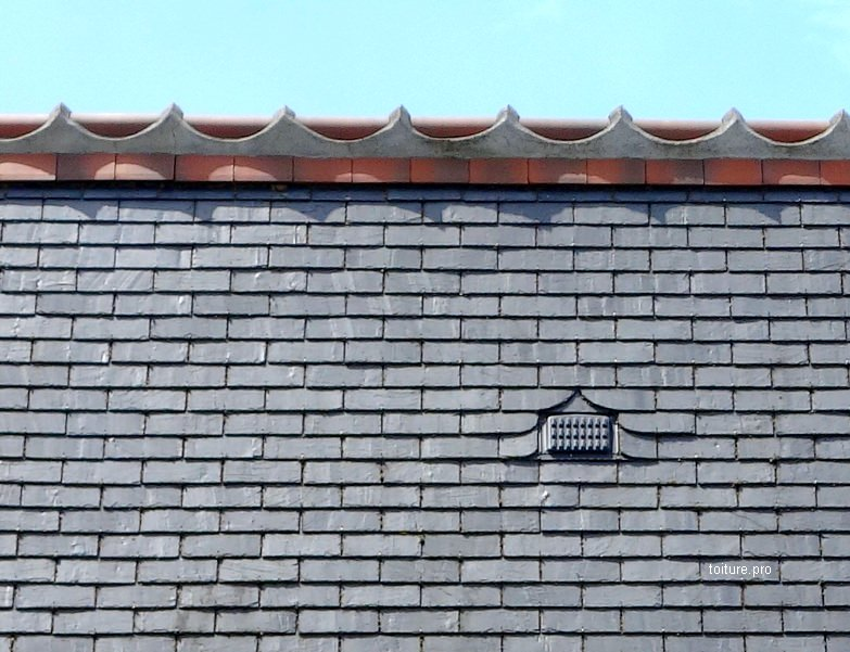 Embarrure sur le faîtage d'une toiture en ardoise avec doublis en tuiles et crêtes de faîtage.