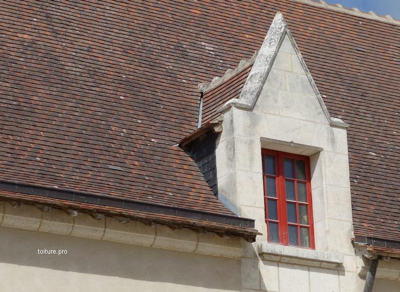 Lucarne à gâble sur une toiture en tuiles.
