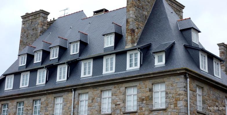 Lucarnes rampantes sur une toiture en ardoises rénovée.