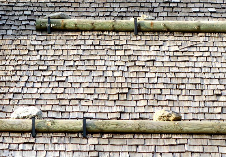Arrêt de neige en bois sur toiture en tavaillons ou bardeaux de bois.