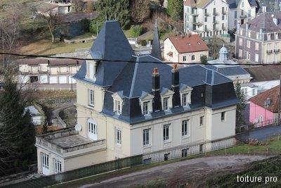 Un toit complexe en ardoises naturelles à Plombières-les-Bains.