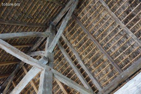 Couverture en roseau sur charpente traditionnelle en bois.